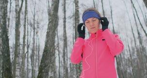 早晨凹凸部的一少女在智能手机采摘训练的音乐轨道的她的手上举行 冬天奔跑 使用现代 影视素材