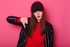时尚年轻女人使用明亮的红色口红,戴着时髦的衬衣、皮夹克和黑帽子 厚颜无耻的tenager显示手指下来 免版税图库摄影