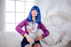 时尚畸形人 魅力微笑的综合性女孩,有蓝色头发的假玩偶拿着花束,当坐时 免版税库存图片