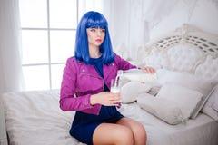 时尚畸形人 魅力综合性女孩、假玩偶有空的神色的和蓝色头发倒牛奶入玻璃一会儿 免版税库存照片