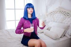 时尚畸形人 魅力综合性女孩、假玩偶有空的神色的和蓝色头发拿着一个玻璃和瓶牛奶 免版税图库摄影