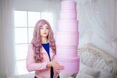 时尚畸形人 魅力综合性女孩、假玩偶有空的神色的和长的淡紫色头发举行桃红色箱子一会儿 库存图片