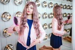 时尚畸形人 魅力综合性女孩、假玩偶有空的神色的和长的淡紫色头发拿着桃红色发刷在 库存图片