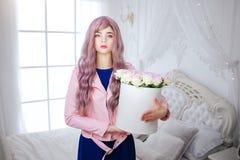 时尚畸形人 魅力综合性女孩、假玩偶有空的神色的和长的淡紫色头发拿着箱子有花一会儿的 免版税库存照片