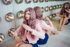 时尚畸形人 魅力综合性女孩、假玩偶有空的神色的和长的淡紫色头发画象在坐 免版税图库摄影