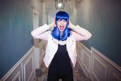 时尚畸形人 魅力综合性女孩,有蓝色头发的假玩偶是叫喊和拿着她的在长的走廊的头 库存图片