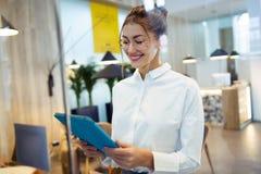 时兴的年轻女实业家与她的在旅馆大厅的数字片剂身分一起使用 库存照片