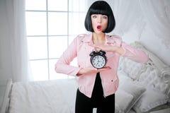 时兴的畸形人 有短的黑色头发的魅力情感美女拿着时钟,当站立在白色时 库存图片