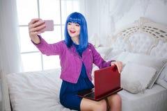 时兴的畸形人 有蓝色头发和时髦构成的魅力微笑的美女拿着计算机并且做着selfie 库存照片