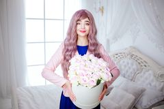 时兴的畸形人 有长的淡紫色头发的魅力微笑的美女拿着有花的白色箱子,当站立时 免版税库存图片