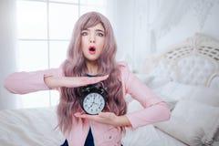 时兴的畸形人 有长的淡紫色头发的魅力情感美女拿着黑时钟,当坐在白色时 免版税库存照片