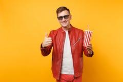 时髦年轻人,红色皮夹克,T恤杉电影影片画象3d玻璃的,拿着杯子苏打或可乐 免版税库存照片