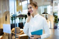时髦的年轻女实业家谈话与她的手机,当举行她的在旅馆大厅时的数字片剂身分 免版税库存照片