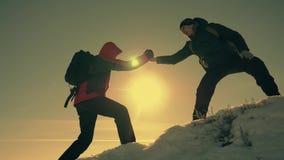 旅游帮助的队友攀登,有背包的人提供了援助一个帮手给他的朋友 配合概念 股票录像