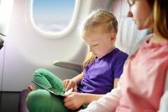 旅行乘飞机的可爱的小女孩 坐由航空器窗口和使用一种数字式片剂的孩子在飞行期间 图库摄影