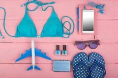 旅行概念-夏天women'带着蓝色泳装、太阳镜、智能手机、触发器一点飞机和手提箱的s时尚 免版税库存图片