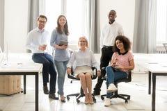 摆在为画象的不同的愉快的雇员小组在办公室 库存图片