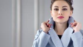 摆在昂贵的军用防水短大衣的可爱的时尚妇女画象的掀动  影视素材