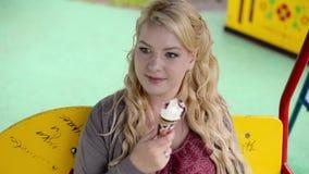 摇摆的年轻可爱的白肤金发的女孩吃和舔冰淇淋的 股票视频