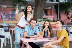 悦目朋友公司是笑,交往和坐在美味的夏天咖啡馆的桌上 图库摄影