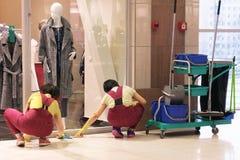 擦净剂的图象在购物中心的 两名妇女抹在地板上的污点 附近的工具 免版税库存照片