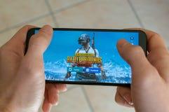 意大利,罗马- 2019年3月7日:拿着有PUBG战场流动比赛的手一个智能手机在显示屏上,社论 库存照片