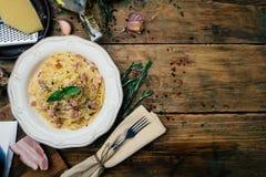 意粉Carbonara 面团alla carbonara用奶油沙司、烟肉和胡椒在一块白色板材 免版税图库摄影