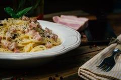 意粉Carbonara 面团alla carbonara用奶油沙司、烟肉和胡椒在一块白色板材 库存图片