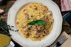 意粉Carbonara 面团alla carbonara用奶油沙司、烟肉和胡椒在一块白色板材 图库摄影