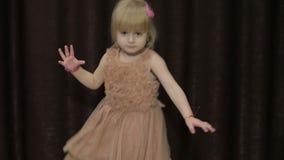 愉快的三岁女孩做面孔和跳舞 逗人喜爱白肤金发的子项 布朗眼睛 逗人喜爱女孩微笑 股票录像