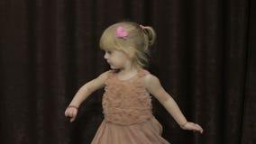 愉快的三岁女孩做面孔和跳舞 逗人喜爱白肤金发的子项 布朗眼睛 逗人喜爱女孩微笑 相当小孩 股票录像