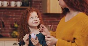 愉快的复活节 妈妈教她的女儿绘的鸡蛋 愉快的家庭为复活节做准备 他们佩带的兔宝宝耳朵 免版税库存照片