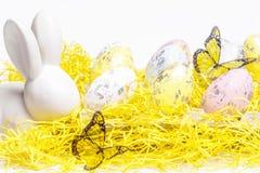 愉快的复活节 在白色背景的复活节白色兔宝宝用复活节彩蛋 复活节与复活节兔子的贺卡 免版税库存照片