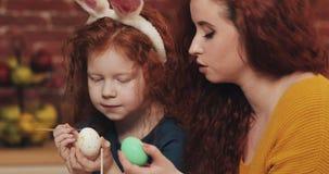 愉快的复活节 母亲和她的小女儿绘的鸡蛋 愉快的家庭为复活节做准备 他们佩带的兔宝宝耳朵 影视素材