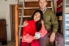 愉快的夫妇坐新的公寓的台阶背景 库存图片