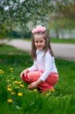 愉快的女孩在蒲公英草甸享受夏时 库存图片