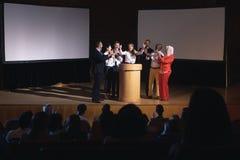 愉快的女实业家身分在观众席的阶段有同事的 免版税库存照片