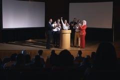 愉快的女实业家身分在观众席的阶段有同事的 免版税库存图片