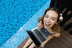 愉快的女性看的照相机上面画象与膝上型计算机的  免版税库存照片