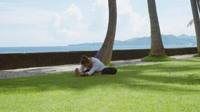 愉快的妇女做瑜伽实践和舒展下来到腿在海洋海滩、美好的背景和自然声音 股票录像