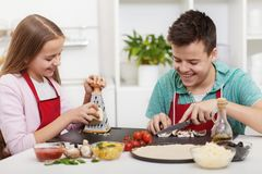 愉快的少年获得乐趣在准备比萨的厨房 图库摄影