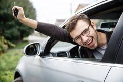 愉快的年轻人从车窗偷看,当看照相机时 他把握关键在他的右手 抽奖 免版税库存照片