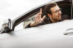 愉快的年轻司机从窗口偷看,当挥动对某人用他的手时 友好的司机概念 免版税库存照片