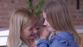 愉快的母性,一点微笑的儿童女孩在家告诉心爱的在耳朵的妈咪耳语的秘密