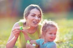 愉快的童年–家庭吹汤泡沫并且做泡影 免版税库存照片