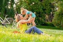 愉快的童年-培养她的女孩孩子的年轻母亲  免版税库存图片