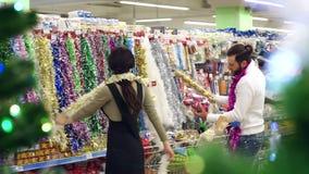 愉快的爱恋的夫妇买的圣诞装饰和礼物圣诞节的 股票录像
