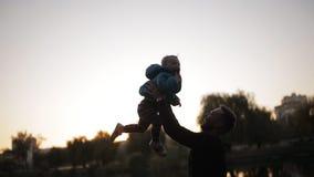 愉快的父亲剪影投掷小儿子在秋天公园以湖为背景 股票视频