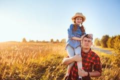 愉快的走在夏天草甸的父亲和女儿,有乐趣和使用 免版税库存照片