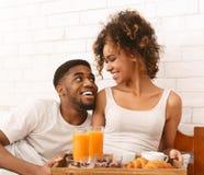 愉快的黑夫妇在床上的享用早餐 免版税库存图片